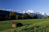 Barn on meadow, snowcovered Wetterstein range in background, Garmisch-Partenkirchen, Upper Bavaria, Bavaria, Germany