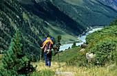 mountaineerer descending from Ölgrubenjoch with view to lake Gepatschsee, Ötztal range, Tyrol, Austria