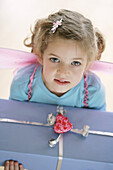 Girl (3-4 years) wearing butterfly wings holding a present