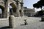 Tourist kneeling down with camera at the Arch of Constantine, Colosseum in the background, Rome, Italy