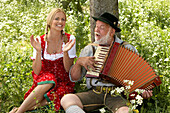 Mature man playing melodeon, woman clapping hands