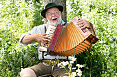 Man wearing bavarian costume leaning against a tree while playing melodeon