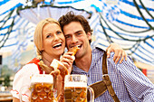 Couple with beer and pretzel in a beer tent