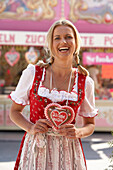 Mid adult woman wearing dirndl dress with a chocolate heart
