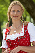 Mid adult woman wearing dirndl dress smiling at camera