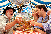 Couple and a mature man clinking beer glasses in a beer tent