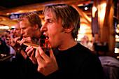 Men drinking schnaps from a ski, shot ski, Caribou Lodge, Banff, Alberta, Canada