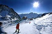 Skiers on run to alpine hut Bella Vista, Schnalstal, South Tyrol, Italy