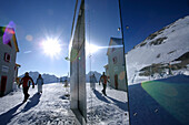 Reflection of skiers and alpine hut Bella Vista on facade, Schnals valley, South Tyrol, Italy
