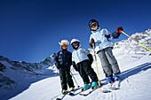 Three children on a ski slope, Lazaun Upper Station, Schnalstal, South Tyrol, Italy