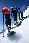 Three men, skiers, about to ski down a slope, Galzig peak, St Anton, Tyrol, Austria