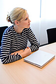 Young woman sitting at conference table with laptop, Luxembourg
