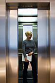 Young woman carrying a laptop standing in an elevator, Luxembourg