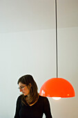 Young woman wearing spectacles looking down, lamp in foreground, Munich, Bavaria, Germany
