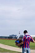 Young man wearing a football shirt playing accordion, Berlin, Germany