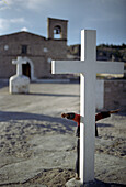 White cross in front of church, a child is hiding behindthe cross, Creel, Mexico