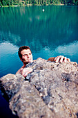Young man climbing, Lake Alpsee, Schwangau, Bavaria, Germany
