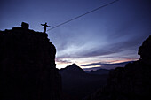 Young man balancing over a rope between to rocks, Oberstdorf, Bavaria, Germany
