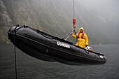 Raising Zodiac onto MS Bremen, Milford Sound, Fiordland National Park, South Island, New Zealand