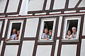Spectators looking out through windows of a timberframe house, Schlitz International Festival, Schlitzerlaender Trachten- und Heimatfest, Schlitz, Vogelsberg, Hesse, Germany