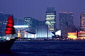 Old Dhow in front of Hong Kong skyline at night, Hong Kong, China
