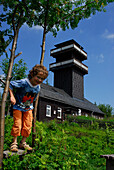 A child, boy, jumping from a bench in front of Leipziger Turm, Schmiedefeld, Thuringia, Germany