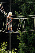 A child, boy, climber, on a high rope course, in Steinach, Thuringia, Germany