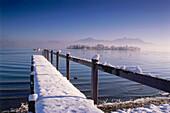 Snow covered footbridge at Lake Chiem, Frauenchiemsee, Chiemgau, Bavaria, Germany