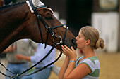 Young woman kissing horse, Ising, Chieming, Chiemgau, Upper Bavaria, Germany