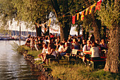 Frauenchiemsee, island feast in July, people sitting on benches under trees by the lake Chiemsee, Chiemgau, Upper Bavaria, Germany