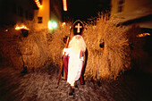 Santa Claus and Buttnmandl, young men dressed in straw, roaming the town during advent, Berchtesgaden, Upper Bavaria, Germany