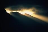 Sunrays through darkness above Pali Ridge, Oahu, Hawaii