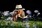 Young woman lying on meadow while reading a book, Icking, Bavaria, Germany