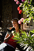 Young woman sitting in front of a house while reading a book, Brannenburg, Upper Bavaria, Bavaria, Germany