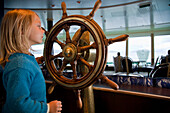 A girl, child, playing with the ships steering wheel on board a Hurtigruten post ship, Norway