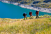 Three young people hiking, reservoir Lago di Lucendro, Gotthard, Canton of Ticino, Switzerland