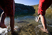 Two young men bathing in lake Laghi d'Orsirora, Gotthard, Canton of Ticino, Switzerland, MR