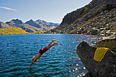 Young man jumping into lake Lago d'Orsino, Gotthard, Canton of Ticino, Switzerland
