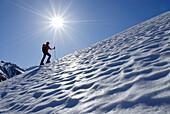 Backcountry skier ascending Leutkircher Huette, Lechtal range, Vorarlberg, Austria