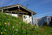 Female hicker sitting in front of alpine hut, Hinterkaiserfeldenalm with view to Wilder Kaiser range, Kaiser range, Tyrol, Austria