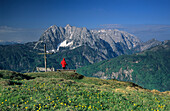 Hiker near summit cross of mount Schnappen, view to Wilder Kaiser range, Kaiser range, Tyrol, Austria