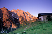 Alpine hut in front of Wilder Kaiser range in alpenglow, Wilder Kaiser, Kaiser range, Tyrol, Austria