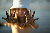 Girl (4-5 years) showing muddy hands, Spiekeroog island, East Frisian Islands, Lower Saxony, Germany