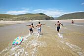 Maori boys running in Waimamaku river, Waimamaku beach on westcoast, near Opononi, Hokianga Harbour, Northland, North Island, New Zealand