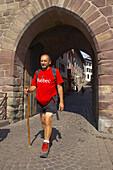 A man, pilgrim walking through the city gate, St. James Way, St. Jean-Pied-de-Port, Euskadi, Pyrenees, Department Pyrénées-Atlantiques, France