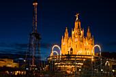 El Sagrat Cor, church, and carousel of the amusement park, Tibidabo, Barcelona, Catalonia, Spain