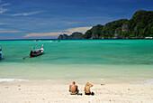 Couple sitting on the beach, Ao Ton Sai, Ko Phi Phi, Krabi, Thailand