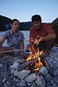 Couple sitting at campfire, Sylvenstein lake, Bavaria, Germany