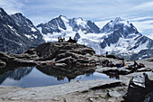 Hikers at the top of a mountain pass, Fuorcla Surlej, Bernina Range, Upper Engadin, Engadin, Grisons, Switzerland