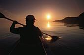 Junge Frau in einem Kajak paddelt bei Sonnenuntergang auf dem Gardasee, Provinz Verona, Veneto, Italien